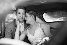 wedding couple sitting inside a car