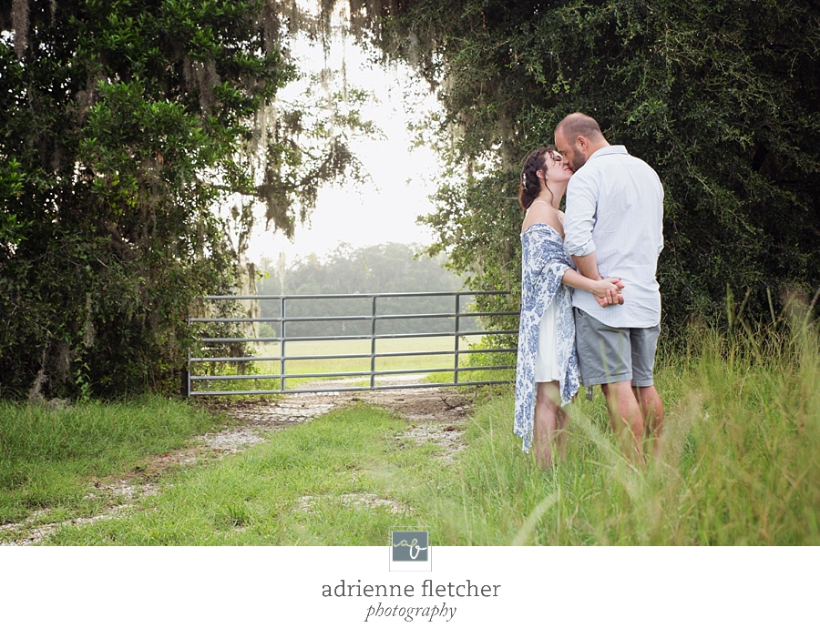 engaged couple kissing in a field