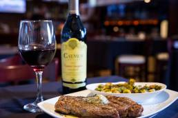 close up of steak dinner with wine bottle
