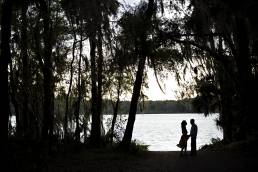 silhouette of couple by lake