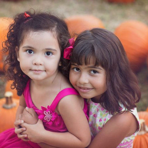 sisters in a pumpkin patch
