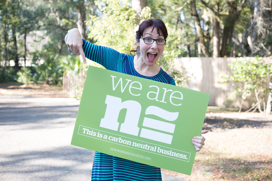 Adrienne Fletcher Photography's owner holding a We are Neutral sign