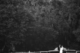 BW image of couple under tree with car