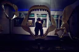 bride and groom in museum behind shark jaws
